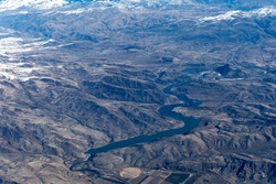 Aerial View of Idaho mountains and snake river from the sky while inside an airplane. View of brown mountains and trees covered with snow