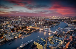 Aerial view of illuminated London, UK, during evening time featuring the Tower Bridge, Thames river and the modern skyscrapers of Canary Wharf