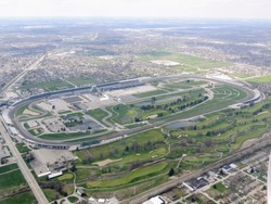 Aerial view of Indianapolis 500, an automobile race held annually at Indianapolis Motor Speedway in Speedway, Indiana through clouds. View from airplane.