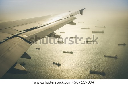 Aerial view of industrial cargo ships fleet moving to the harbour of Singapore in south east Asia - Retro contrasted dramatic filter