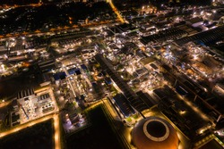 Aerial view of Industrial factory with chemical refinery and building material glowing light at night