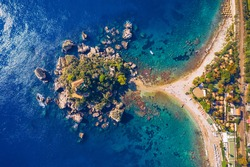 Aerial view of Isola Bella in Taormina, Sicily, Italy. Isola Bella is small island near Taormina, Sicily, Italy. Narrow path connects island to mainland Taormina beach in azure waters of Ionian Sea.
