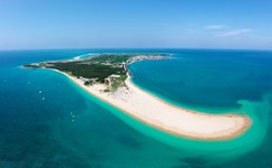 Aerial view of Jibei Island, a famous tourist destination for water sports in Baisha, Penghu County, Taiwan, with a beautiful sandspit extruding into the turquoise seawater under blue clear summer sky