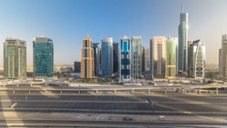 Aerial view of Jumeirah lakes towers skyscrapers during all day timelapse with traffic on sheikh zayed road and metro line. Shadows moves very fast and reflections on a glass