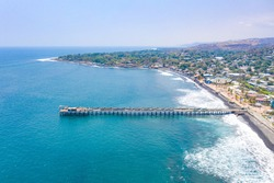 Aerial  view of La Libertad beach in El Salvador, where you can see part of the coastal area and its pier of the sea, with a beautiful blue sky.
