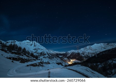 Aerial view of La Thuile village glowing in the night, famous ski resort in Aosta Valley, Italy. wonderful starry sky and majestic mountain landscape illuminated by the moon.