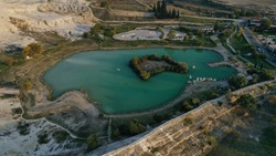 Aerial view of lake and famous Pamukkale travertines hot thermal springs in Turkey, Hierapolis ancient town. Unesco World Heritage Site.