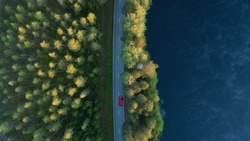 Aerial view of lake, forest and road at misty morning. Red car driving through the forest at sunrise. Highway through deep forest.