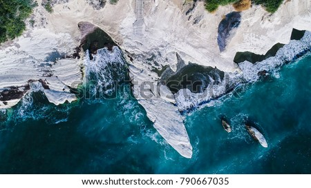 Aerial view of landmark big white chalk rock at Governor's beach caves, Limassol, Cyprus. The steep stone cliffs and deep blue sea waves crushing in coves and dark sand from above.