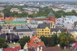 Aerial view of Latvian War Museum, (before it was called Powder Tower) and Riga Old Town from Saint Peter church on cloudy, foggy and rainy day, Riga, Latvia. Soft selective focus
