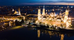 Aerial view of lighted Roman Catholic Basilica Our Lady of Pillar on background of Zaragoza cityscape and Ebro river at dusk, Spain..