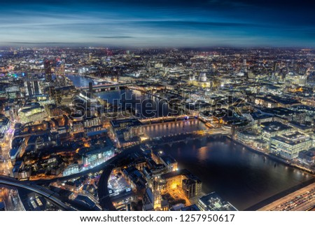 Aerial view of London by night with the famous bridges along the river Thames and major sightseeing attractions, UK
