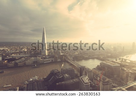 Aerial view of London with The Shard skyscraper and Thames river at sunset with grey clouds in the sky. Vintage filter applied.