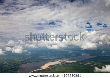 Aerial view of lowland of river during a flight beside clouds in the during summer day.