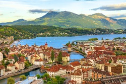 Aerial view of Lucerne skyline and lake Lucerne with Mount Rigi and its peak Rigi-Kulm in the Canton of Lucerne, Switzerland. Amazing panorama with sunset orange clouds and green hills.