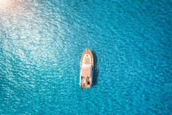 Aerial view of luxury yacht in transparent blue sea at sunset in summer in Mallorca, Spain. Colorful landscape with boat, bay, clear azure water. Top view from air. Travel. Seascape with motorboat