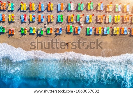 Aerial view of lying woman on the beach with colorful chaise-lounges. Beautiful young woman on the sea at sunset in Oludeniz, Turkey. Top view. Seascape with girl, azure water and waves. Holiday