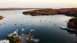 Aerial view of maine coastal harbor - drone picture of lobster boats with the ocean inside a marina  sunset - kennebunk maine round pond maine coastal maine