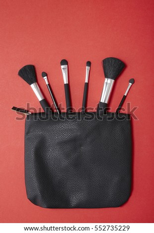 Aerial view of make up brushes spilling out of a black cosmetics bag on to a bright red background