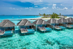 Aerial view of Maldives island, luxury water villas resort and wooden pier. Beautiful sky and ocean lagoon beach background. Summer vacation holiday and travel concept. Paradise aerial landscape pano