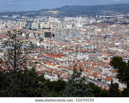 Aerial view of Marseilles city with all the colored roofs of the buildings and the mountain behind, France
