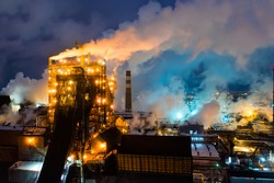 Aerial view of metallurgical plant blast furnace at night with smokestacks and fire blazing out of the pipe. Industrial panoramic landmark with blast furnance of metallurgical production