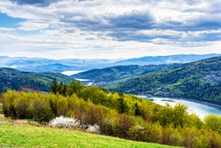 Aerial view of Miedzybrodzie town in Beskid Maly mountain range. Lake and dam in the background. Beautiful spring panorama.
