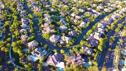 Aerial view of modern suburban neighborhood from above with green landscapes and trees, pools, and houses, in Las Vegas, Nevada