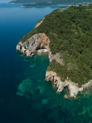 Aerial view of Mogren beach, beautiful bay, steep stone cliff with green forest, emerald transparent Adriatic sea, stones underwater on seabed. Sailing boat. Budva, Montenegro. Wild unspoiled nature