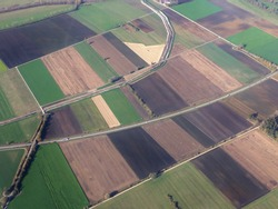 Aerial view of monoculture crop fields and symmetrical countryside panorama, Bavaria, Germany. Concept of industrial farming, monotone landscape architecture destroying biodiversity and local species