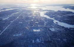 Aerial view of Montreal, Quebec, Canada in winter. St Lawrence river is frozen and the sun is reflected in the ice coverage