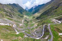 Aerial view of mounrain road Transfagarasan in Romania in summer, difficult curvy rock way