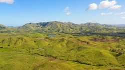 Aerial view of mountains and hills with rainforest and green grass under a blue sky with clouds on a Sunny summer day. Bohol, Philippines.