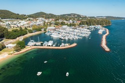 Aerial view of Nelson Bay marina, breakwater, and town, with aqua waters of Port Stephens, Australia