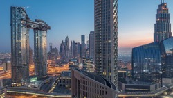 Aerial view of new and tall buildings with busy roads timelapse. Transition from night to day in Dubai Downtown from above with traffic on roads, Dubai, United Arab Emirates