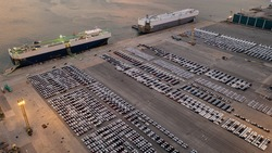 Aerial View of new cars parked at the parking area of automobile factory. Waiting for RORO transport