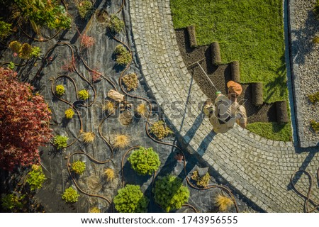 Aerial View of New Residential Garden Developing by Caucasian Landscaping Worker. Planting Flowers, Decorative Trees and Natural Grass Installation Stockfoto ©