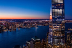 Aerial view of New York city and one world trade center brookfield place at dusk.