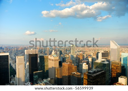Aerial view of New York City at dusk with warm sunset color and cloud.