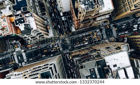 Aerial view of New York downtown building roofs. Bird's eye view from helicopter of cityscape metropolis infrastructure, traffic cars, yellow cabs moving on city streets and crossing district avenues #1332370244