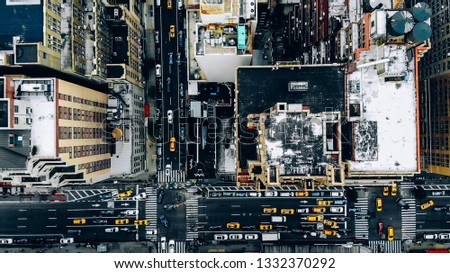 Aerial view of New York downtown building roofs. Bird's eye view from helicopter of cityscape metropolis infrastructure, traffic cars, yellow cabs moving on city streets and crossing district avenues #1332370292