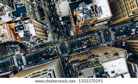 Aerial view of New York downtown building roofs. Bird's eye view from helicopter of cityscape metropolis infrastructure, traffic cars, yellow cabs moving on city streets and crossing district avenues #1332370295