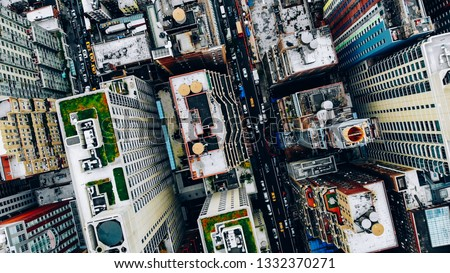 Aerial view of New York downtown building roofs with water towers. Bird's eye view from helicopter of cityscape metropolis infrastructure, traffic cars moving on city streets and district avenues #1332370271