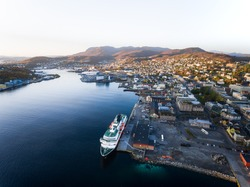 Aerial view of Norwegian Hurtigruten cruiseship in the small harbour of Harstad.