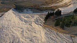 Aerial view of observation deck and thermal pools hot springs travertine terraces of Pamukkale natural park, white cotton castle, snow white mountains with carbonate mineral milky pools, Turkey