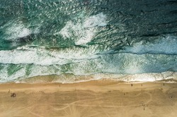 Aerial view of ocean beach. Sand beach and sea view from above. Beach aerial view of ocean water and sand shore. Aerial shot of beach emphasizing the scale of people and nature