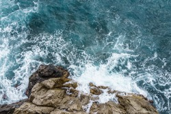 Aerial view of ocean wave crashing on rocky cliff with white spray and foam on deep blue sea water after storm.