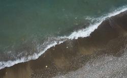 Aerial view of ocean waves braking on a sandy beach. Nature background. Sea water