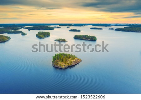Aerial view of of small islands on a blue lake Saimaa. Landscape with drone. Blue lakes, islands and green forests from above on a cloudy summer morning. Lake landscape in Finland. Foto stock ©