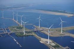 Aerial view of offshore wind turbine farm at sluice Krammersluizen at river Volkerak and Krammer, Netherlands. National road N257 at dam Philipsdam crosses the water. On the horizon Bruinisse, Zeeland